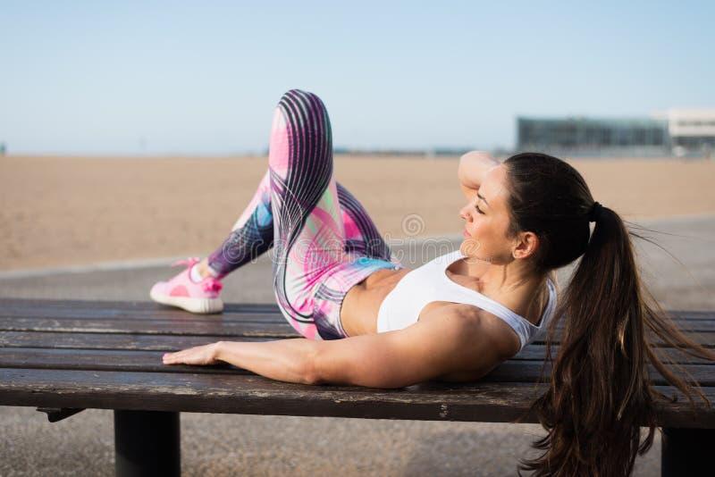 Femme de forme physique faisant des craquements à la plage image stock