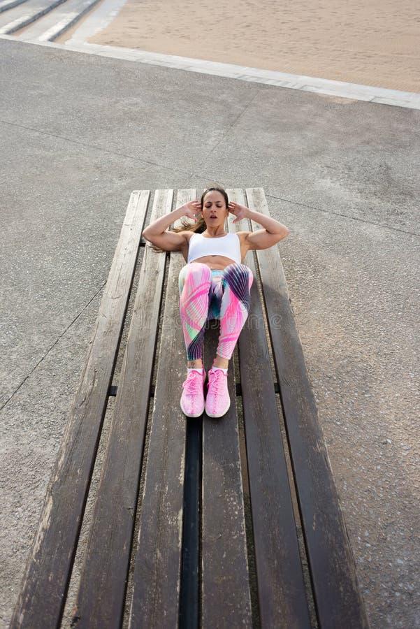 Femme de forme physique faisant des craquements dehors photos stock