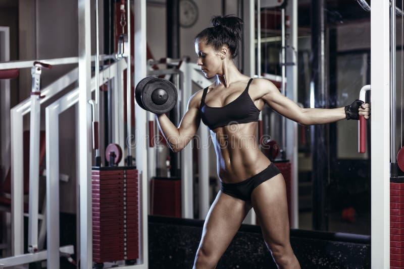 Femme de forme physique faisant des exercices avec l'haltère dans le gymnase images libres de droits