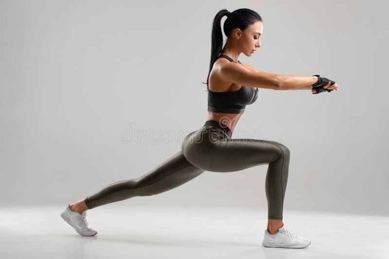 Femme de forme physique faisant des exercices de mouvements brusques pour la formation de s?ance d'entra?nement de muscle de jamb photo stock