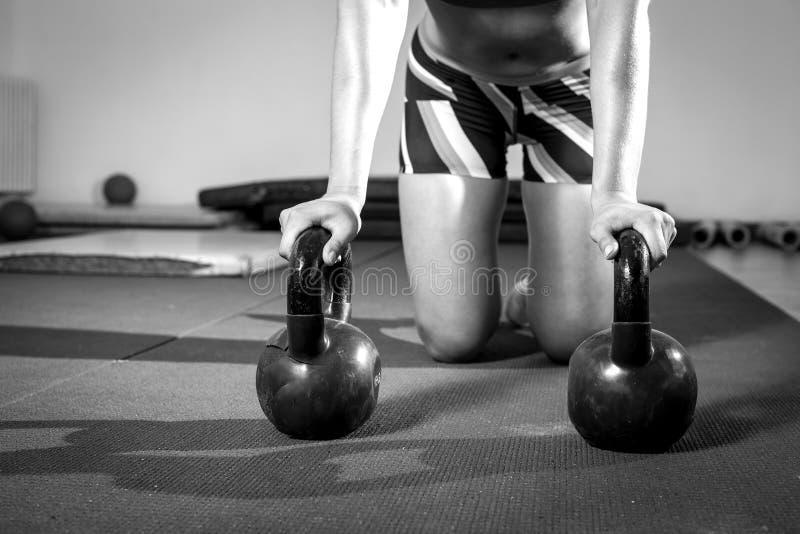Femme de forme physique faisant des pousées avec des kettlebells photographie stock libre de droits