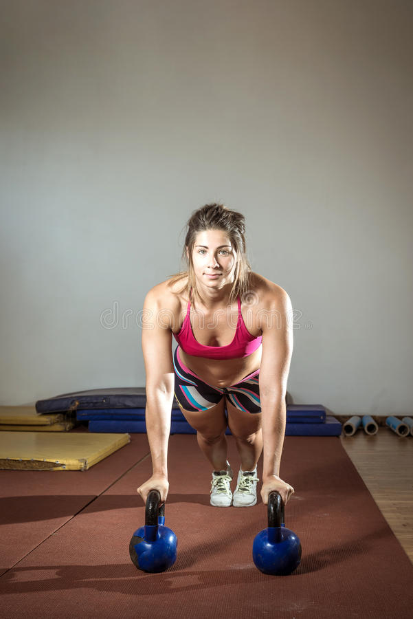 Femme de forme physique faisant des pousées avec des kettlebells photos libres de droits