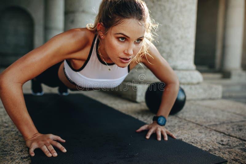 Femme de forme physique faisant des pousées sur un tapis de yoga images libres de droits