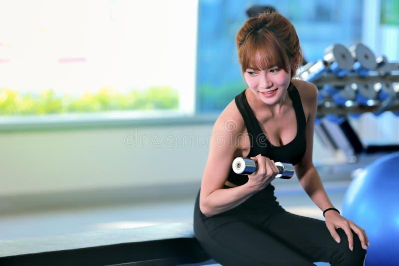 Femme de forme physique faisant des séances d'entraînement de biceps avec des haltères dans un gymnase image stock