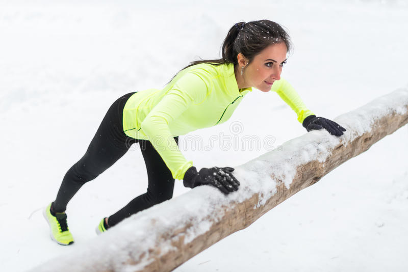 Femme de forme physique faisant la formation extérieure d'hiver de pousées photos stock