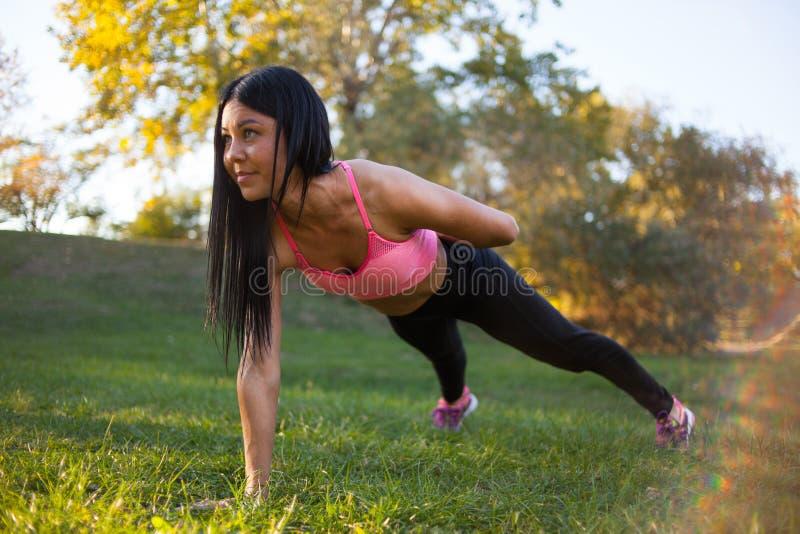 Femme de forme physique faisant la séance d'entraînement d'exercice de noyau de planche sur l'herbe images stock