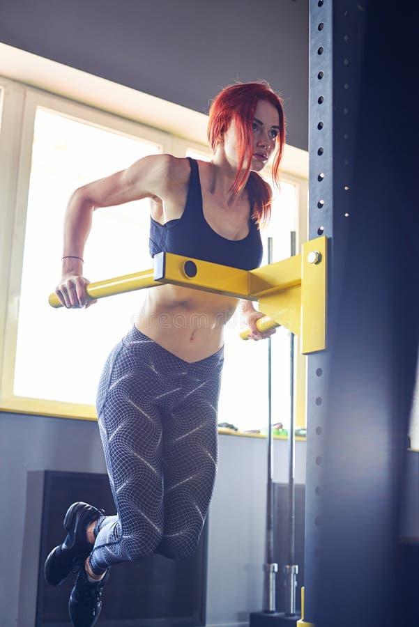 Femme de forme physique faisant le levage sur la barre de gymnase photo libre de droits
