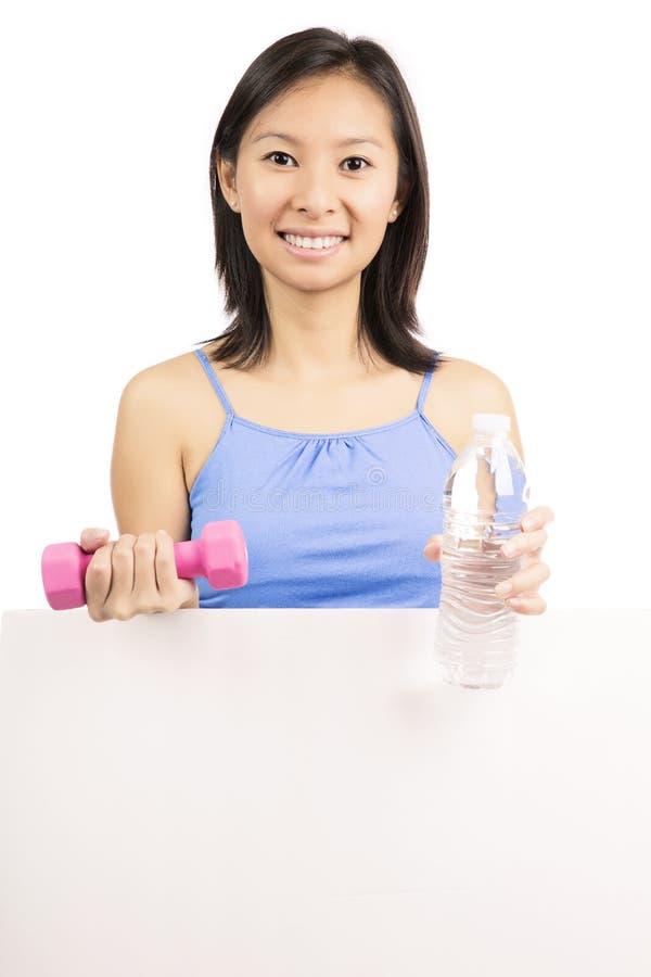 Femme de forme physique montrant le panneau d'affichage photographie stock