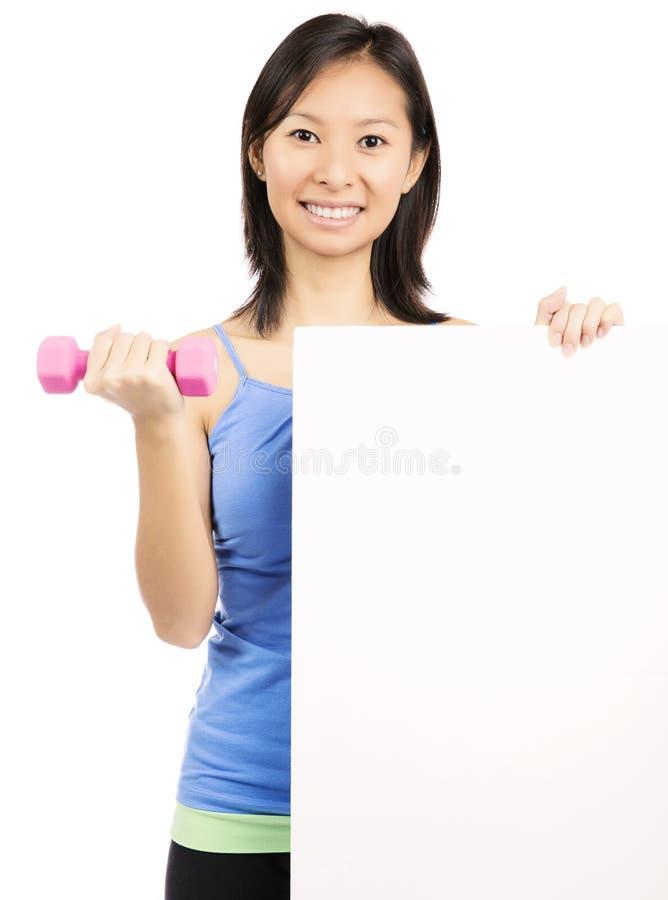 Femme de forme physique montrant le panneau d'affichage images libres de droits