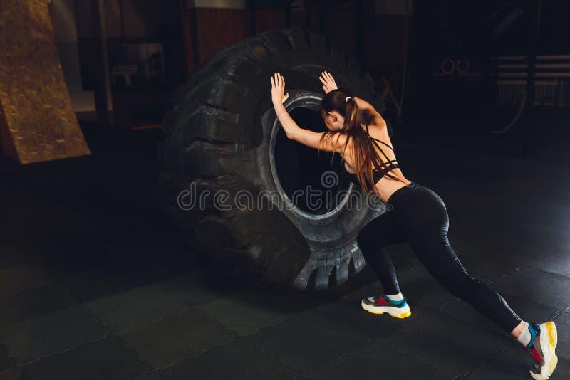 Femme de forme physique renversant le pneu de roue dans le gymnase Athl?te f?minin convenable ?tablissant avec un pneu ?norme Vue image libre de droits