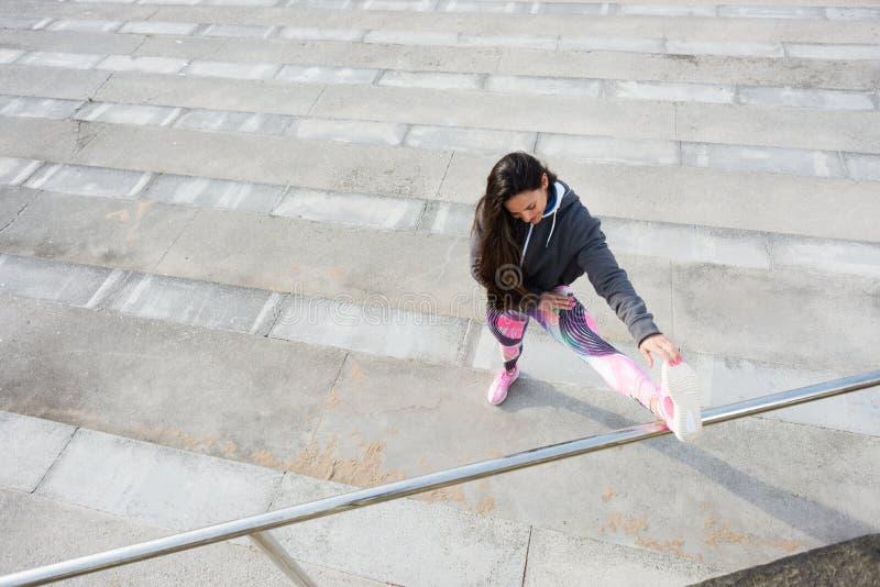 Femme de forme physique s'étirant avant séance d'entraînement urbaine photographie stock libre de droits