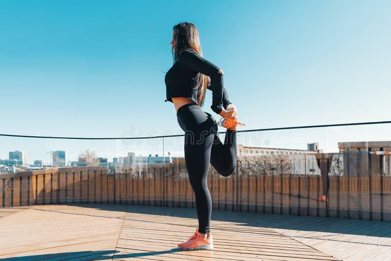 Femme de forme physique s'étirant et s'exerçant dehors dans le milieu urbain images stock