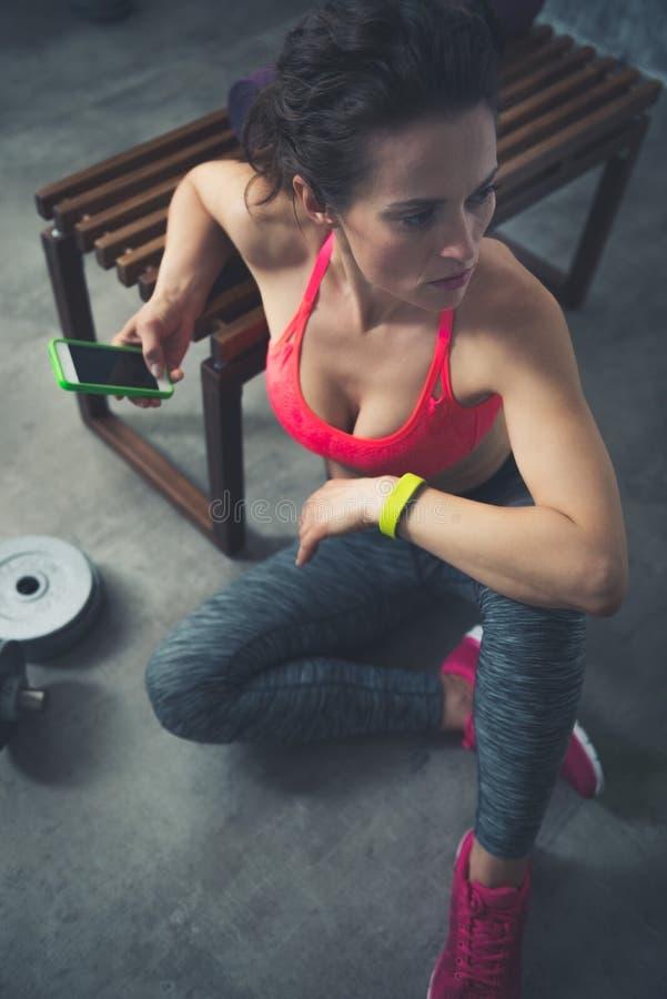 Femme de forme physique s'asseyant dans le gymnase de grenier avec le téléphone portable photos libres de droits