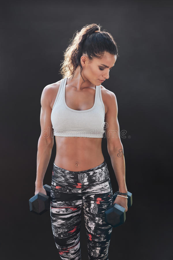 Femme de forme physique s'exerçant avec des haltères image stock