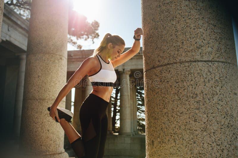 Femme de forme physique s'exerçant dehors un jour ensoleillé image stock