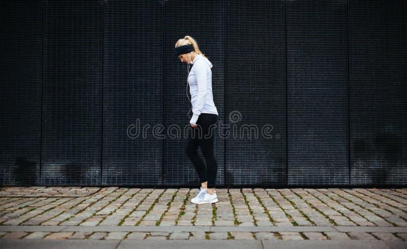Femme de forme physique se préparant à une course de ville images libres de droits