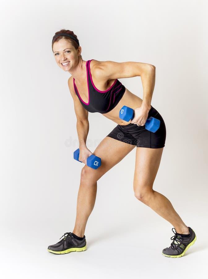 Femme de forme physique soulevant les poids gratuits Sur un fond blanc photos stock