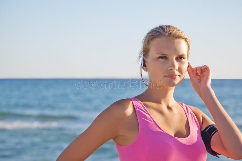 Femme de forme physique sur la plage dans des écouteurs photos stock