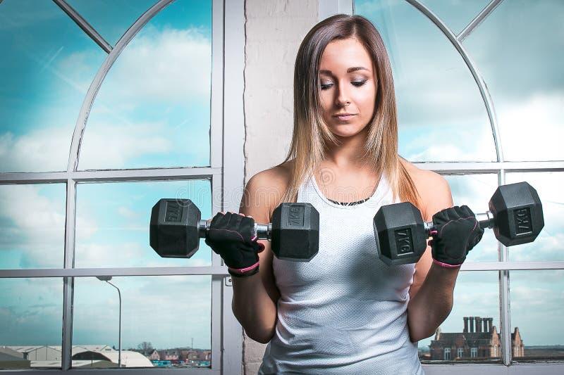Femme de forme physique tenant des haltères photo stock