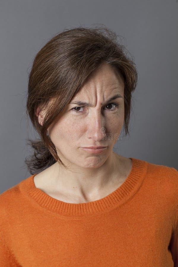 Femme de froncement de sourcils ayant des doutes se plaignant et maugréant avec l'irritation photo stock
