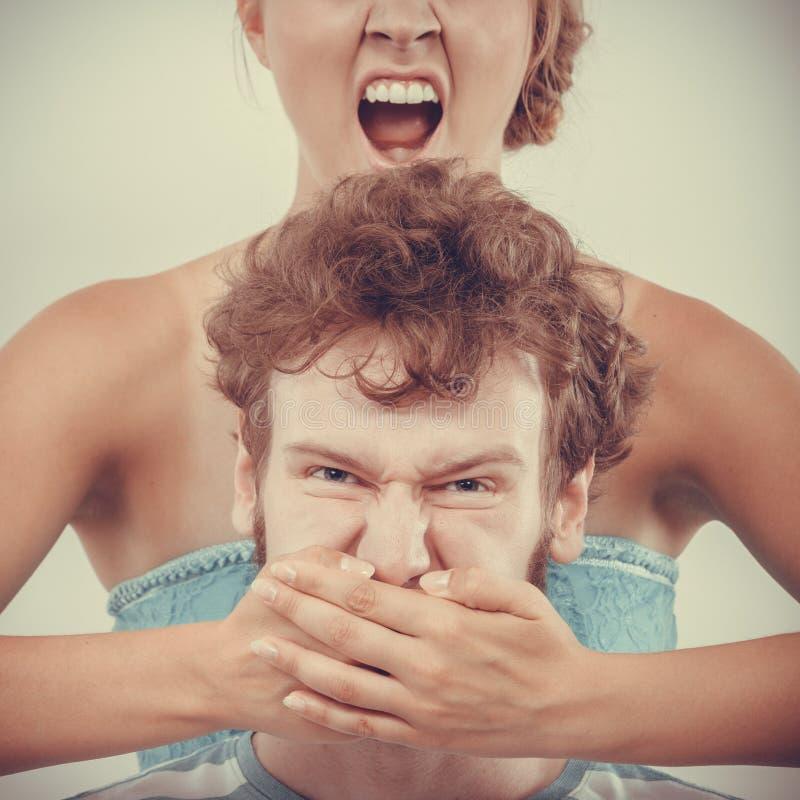 Femme de fureur criant tout en couvrant dites son homme du bout des lèvres photo stock