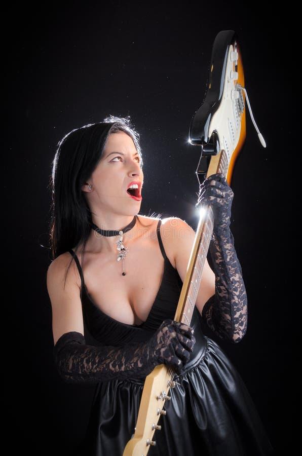 Femme de Goth balançant la guitare électrique dans un geste sensationnel image stock