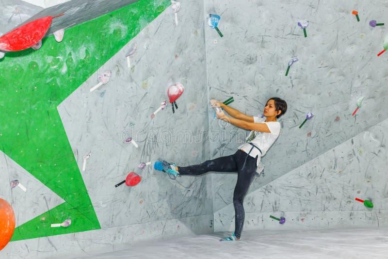Femme de grimpeur de roche accrochant sur un mur s'?levant bouldering, ? l'int?rieur sur les crochets color?s photographie stock