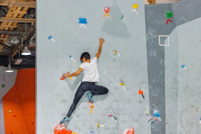Femme de grimpeur de roche accrochant sur un mur s'?levant bouldering, ? l'int?rieur sur les crochets color?s image libre de droits