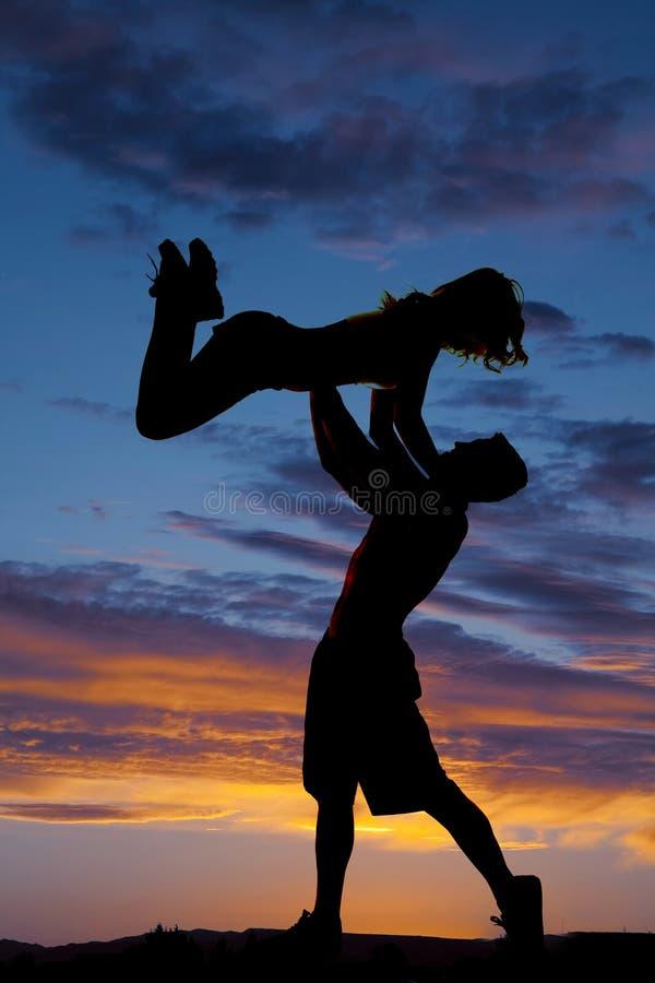 Femme de jet d'homme de couples de silhouette vers le haut de coucher du soleil photo stock