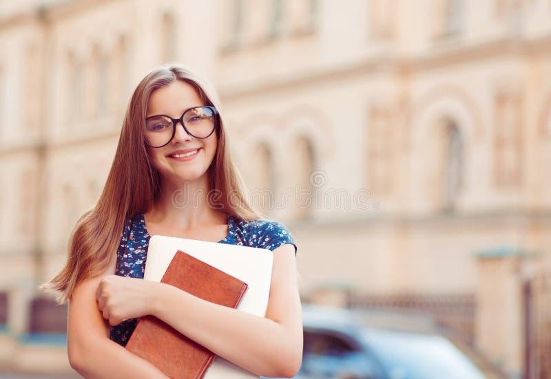 Femme de jeune fille d'?tudiant tenant l'ordinateur portable de livres souriant dehors photo stock