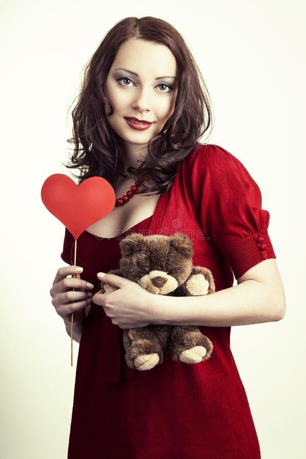 Femme de jour de valentines tenant le coeur et le jouet mou dans des ses mains image stock