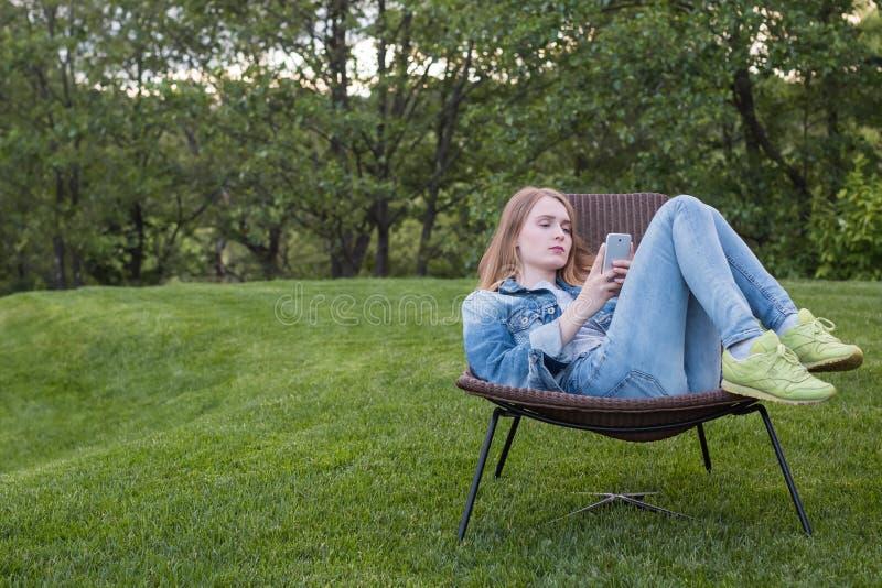 Femme de l'adolescence à l'aide du smartphone en dehors du jardin photos libres de droits