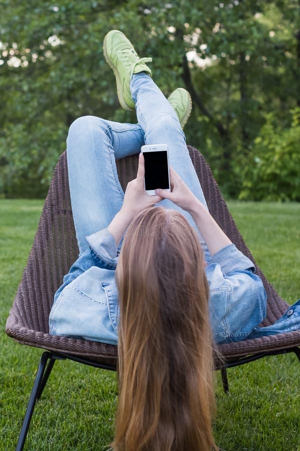 Femme de l'adolescence à l'aide du smartphone en dehors du jardin photos stock