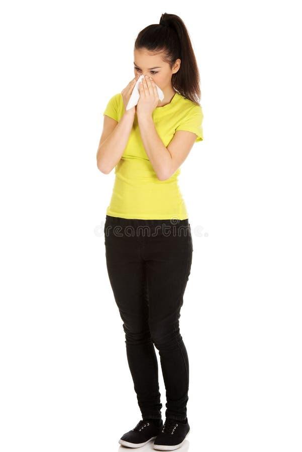 Femme de l'adolescence éternuant au tissu images stock