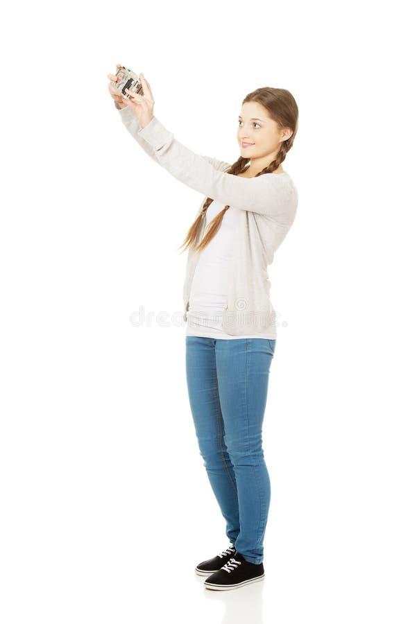 Femme de l'adolescence faisant la photo avec l'appareil-photo photographie stock