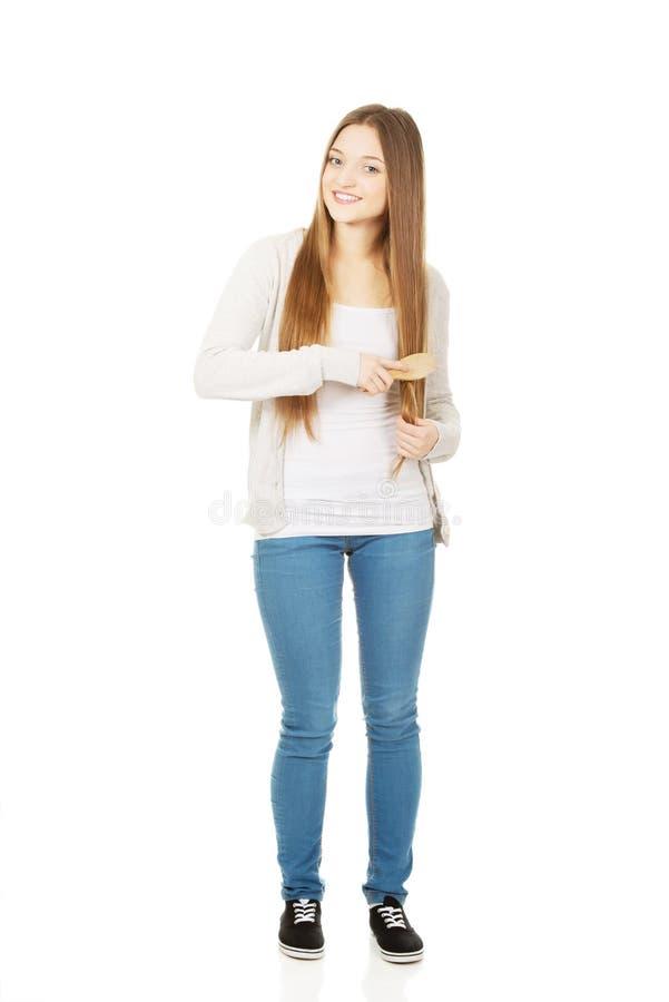 Femme de l'adolescence se brossant les cheveux photo libre de droits