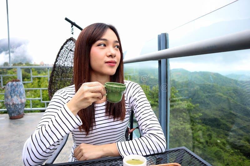 Femme de l'Asie appréciant le beau matin serein regardant le ciel du paysage de paysage de nature de montagnes commençant le café photos libres de droits