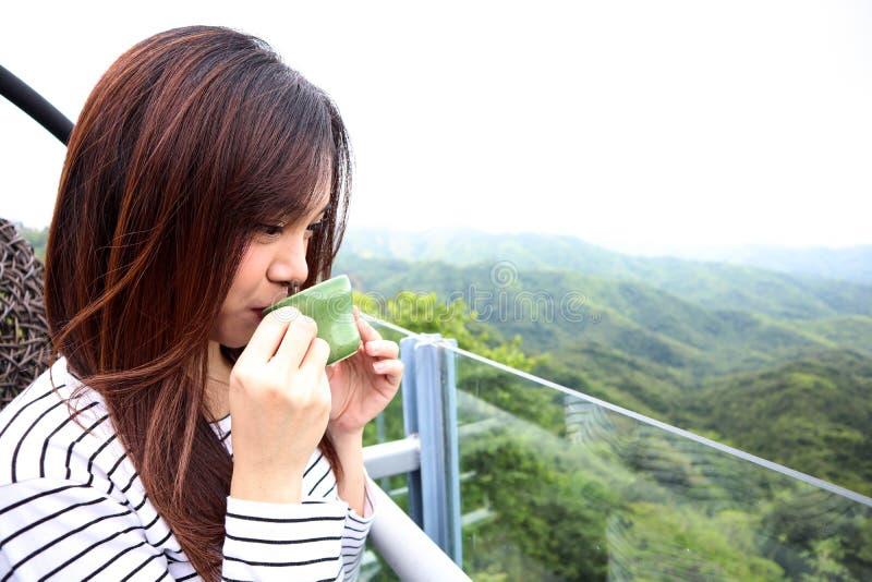 Femme de l'Asie appréciant le beau matin serein regardant le ciel du paysage de paysage de nature de montagnes commençant le café photos stock