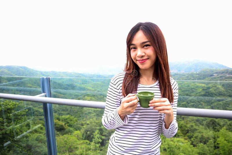 Femme de l'Asie appréciant le beau matin serein regardant le ciel du paysage de paysage de nature de montagnes commençant le café image libre de droits