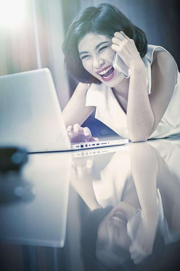 Femme de l'Asie avec le téléphone intelligent et l'ordinateur portable se trouvant sur le plancher photos stock