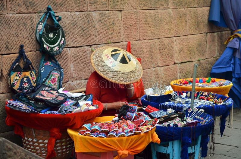Femme de la Chine vendant des souvenirs sur le marché dans Fenghuang photographie stock