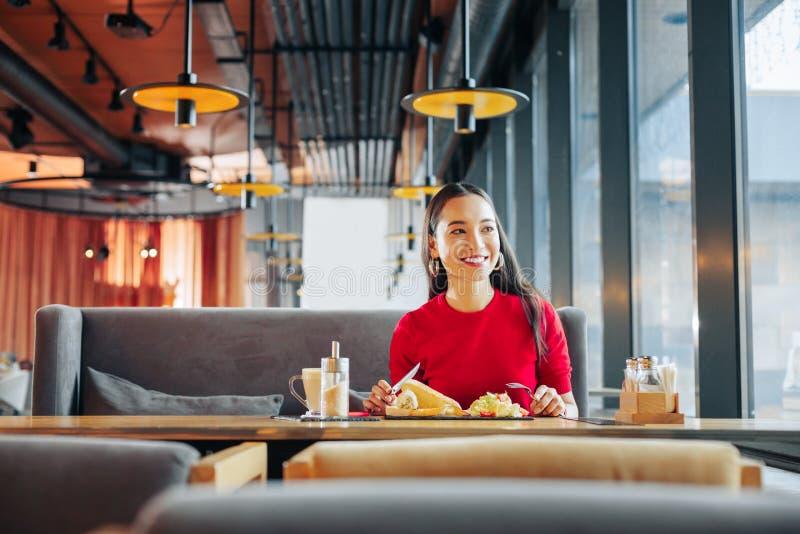 Femme de lancement avec les lèvres rouges mangeant le déjeuner savoureux dans le restaurant image stock