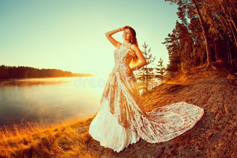 Femme de luxe dans une forêt dans une longue robe de vintage près du lac photo stock