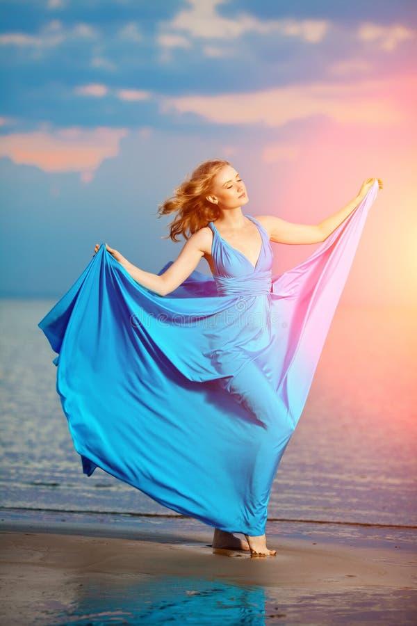 Femme de luxe dans une longue robe de soirée bleue sur la plage beauté photographie stock libre de droits