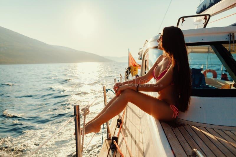 Femme de luxe faisant de la navigation de plaisance en mer au coucher du soleil photos libres de droits