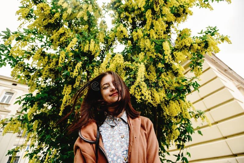 Femme de luxe heureuse élégante ayant l'amusement sous l'autobus de floraison étonnant image libre de droits
