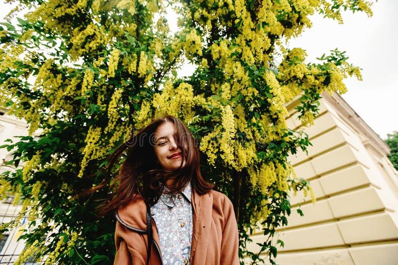 Femme de luxe heureuse élégante ayant l'amusement sous l'autobus de floraison étonnant photographie stock