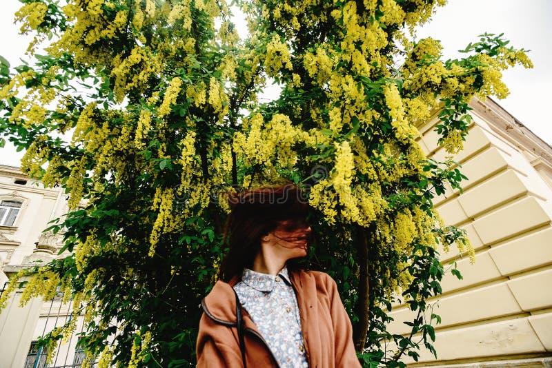 Femme de luxe heureuse élégante ayant l'amusement sous l'autobus de floraison étonnant photographie stock libre de droits