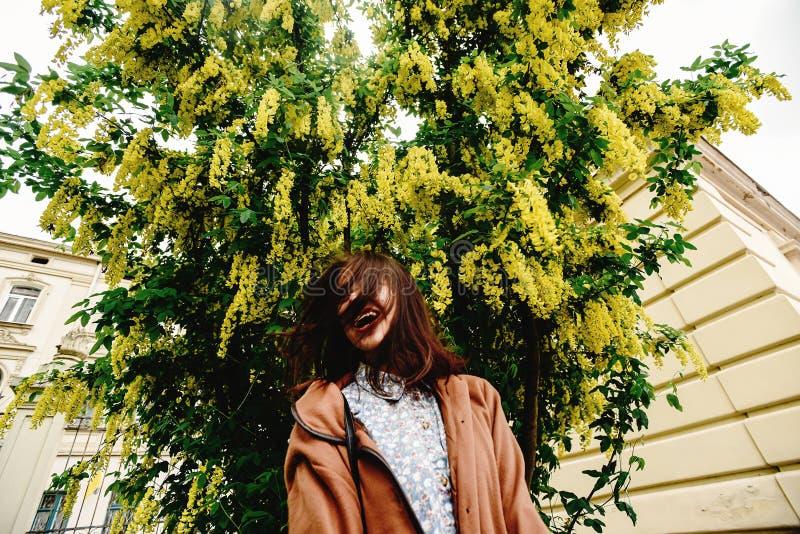 Femme de luxe heureuse élégante ayant l'amusement sous l'autobus de floraison étonnant image stock