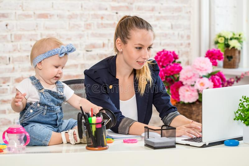 Femme de mère de femme d'affaires avec une fille travaillant à l'ordinateur portable images stock